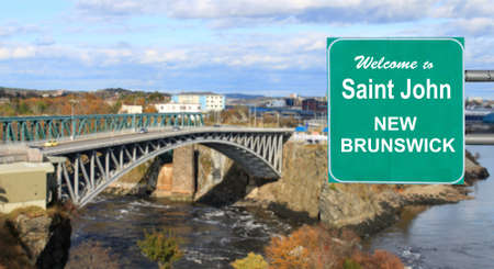 reversing: Welcome to Saint John, New Brunswick, Canada sign with Reversing Falls bridge in the background