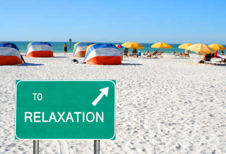 A  to relaxation  sign pointing to people relaxing on beach chairs under umbrellas in Clearwater Beach, Florida, USA photo