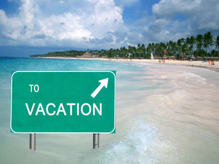 To Vacation sign in the Caribbean ocean with arrow pointing at a tropical beach