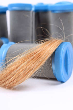 strand of hair: Hot rollers in different sizes  for hairstyling with strand of blonde hair on a white background