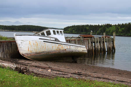beached: Maritime beached and old fishing boat leaning on a wooden pier on the shores of the Bay of Fundy in Maces Bay, New Brunswick, Canada