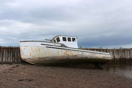 beached: Beached fishing boat leaning against a wooden pier in the Bay of Fund,  Maces Bay, New Brunswick, Canada