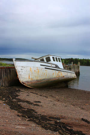 beached: Beached fishing boat leaning against a wooden pier under dark sky in the Bay of Fund,  Maces Bay, New Brunswick, Canada