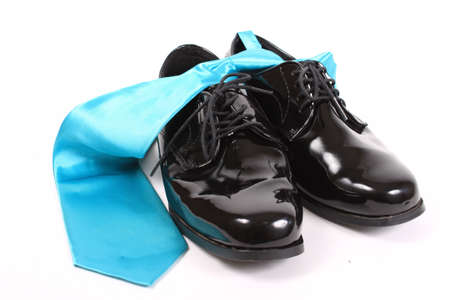 shiny black: Mens shiny lace up formal black shoes with light blue tie on a white background