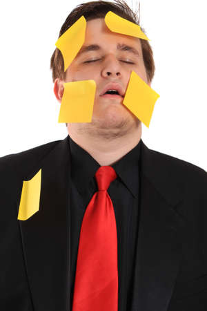 tired businessman: Tired and overwhelmed from work, businessman with yellow sticky note paper on face and suit on a white background