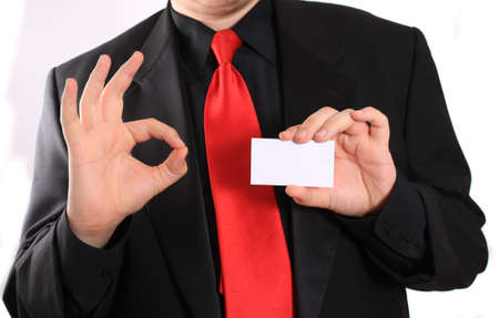 Businessman holding a blank business card in one hand and making an ok gesture in the other on a white background (focus on card) photo