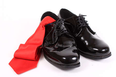 businesswear: Mens shiny lace up formal black shoes with red tie on a white background