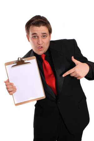 Businessman with funny expression pointing at and holding a clipboard with a blank page on a white background photo
