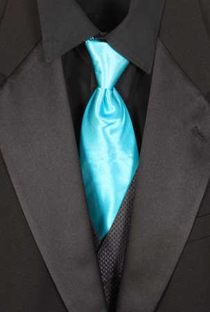 Black dressy formal three piece  suit with shirt, vest  and blue tie photo