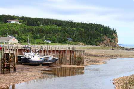 beached: Beached, fishing boats in Alma, on the Bay of Fundy, New Brunswick Editorial