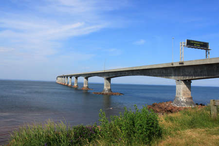 confederation: Confederation bridge connecting New Brunswick to Prince Edward Island with greenery in the foreground Stock Photo