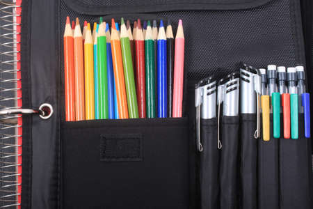pocket book: Colorful sharpened  pencil crayons for school in three ring binder pocket with pens on the side