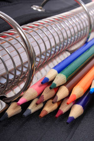 colorful sharpened  pencil crayons for school  beside  three ring binder  Reklamní fotografie