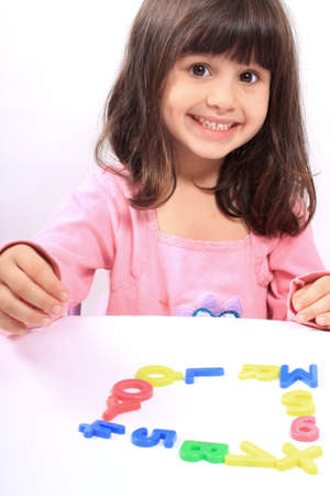 preschoolers: Young little preschool girl with funny expression playing with letters and numbers