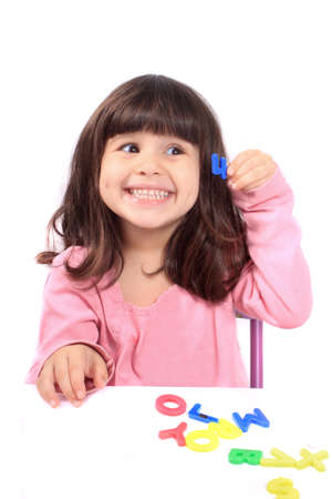 and four of the year: Young little preschool girl with funny expression playing with letters and holding up the number four showing her age Stock Photo
