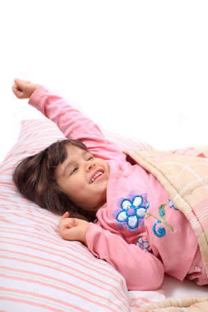 awaken: Cute little girl stretching her arms happily with a smile from waking up in her bed.