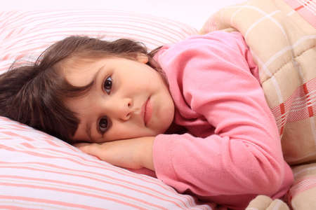 Cute little girl laying in bed and cant fall asleep or is just waking up photo