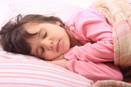 niño durmiendo: Linda niña acostada en la cama para dormir cómodo en la almohada y su manta Foto de archivo