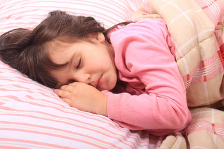 four year old: Cute little girl laying in bed sleeping cozy on her pillow and in her blanket  Stock Photo