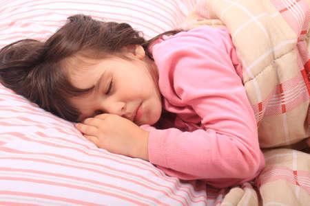 čtyři lidé: Roztomilá holčička, kterou v posteli spí útulný na její polštář a v její deky Reklamní fotografie