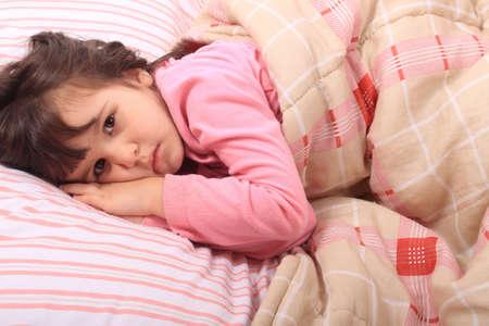 insomnio: Linda niña acostada en la cama y no puede conciliar el sueño o se acaba de despertar