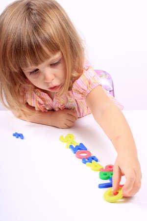 文字と幼児の発達の数字と遊ぶ若い女の子