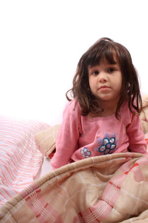 Sleepy little girl just waking up in bed cozy with blanket and messy hair photo