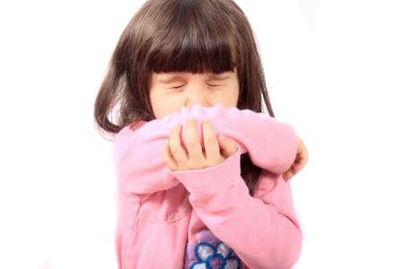 estornudo: Niña enferma estornudos en su manga debido a enfermedad o alergias