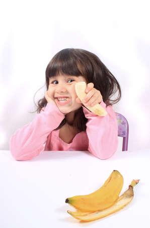 comiendo platano: Niña pequeña haciendo una cara divertida de comer un plátano sano Foto de archivo