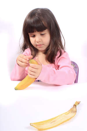 pealing: Young little girl pealing a healthy banana