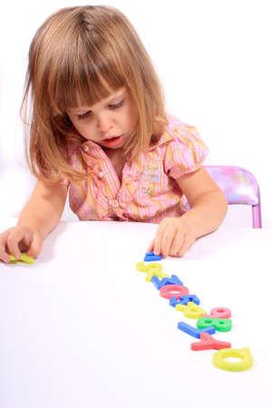 文字と数字の幼児開発と遊ぶ若い女の子 写真素材