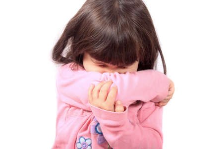 the sleeve: Little sick girl sneezing onto her sleeve because of sickness or allergies