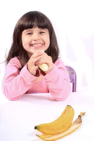 comiendo platano: Niña pequeña sonrisa sana comiendo un plátano
