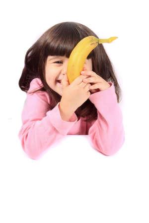 comiendo platano: Joven niña ocultando su rostro con una banana saludable mientras sonriente