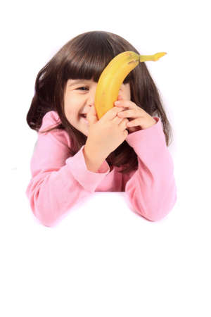 eating banana: Young little girl hiding her face with a healthy banana while smiling