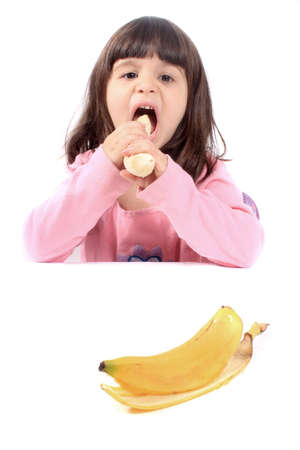 banana: Young little girl making a funny face eating a healthy banana
