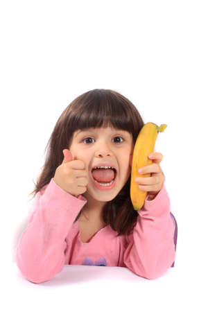 eating banana: Young little girl giving the thumbs up for healthy eathing with a banana