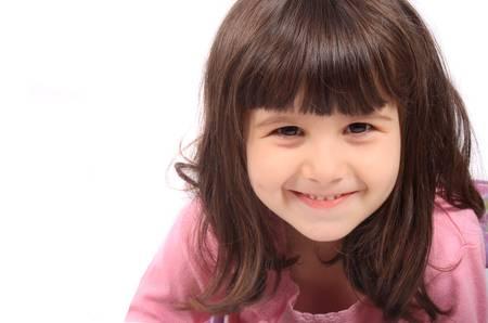 Close-up van de kleine vier jaar oude brunette meisje lachend op een witte achtergrond Stockfoto