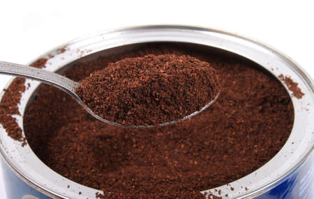 Spoonfull of fresh ground coffee in a can on a white background Banco de Imagens