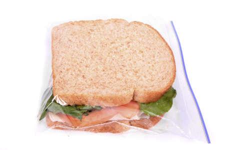 bolsa de pan: S�ndwich de pavo y queso en pan integral con tomate y lechuga dentro de una bolsa con cremallera listo para el almuerzo Foto de archivo