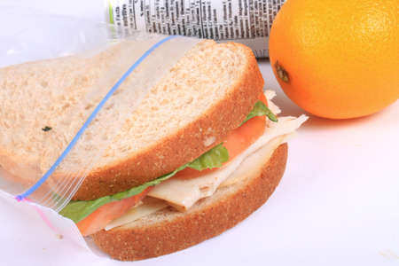 Turkey and cheese sandwich on whole wheat bread with tomato and lettuce inside a zipped bag ready for lunch and orange on the side Archivio Fotografico