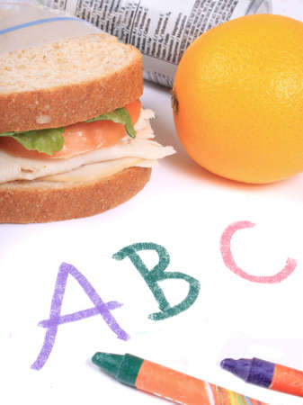 zipped: Turkey and cheese sandwich on whole wheat bread with tomato and lettuce inside a zipped bag ready for lunch and orange and juice can on the side on top of abc paper