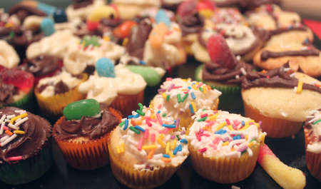 differently: Differently decorated tiny colorful cupcakes with icing, sprinkles, and candy with shallow depth of field