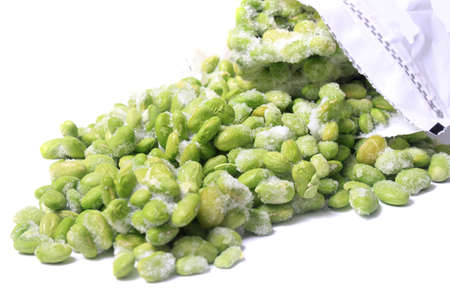 Frozen edamame also known as soybeans coming out of a freezer bag on a white background