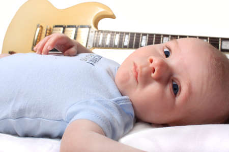 Cute seven week old newborn baby laying with a guitaron white background photo