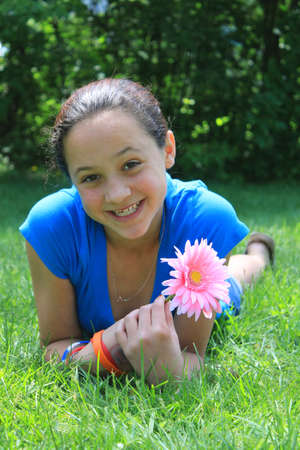 eleven: Pretty eleven year old girl laying on the grass holding a flower outdoors