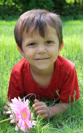 three year old: Cute little three year old boy laying on the grass holding a flower and smiling Stock Photo