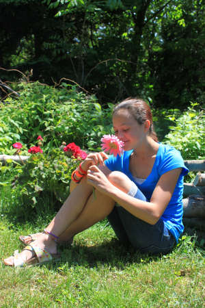 eleven: Pretty eleven year old girl holding and smelling a pink flower outdoors in the garden
