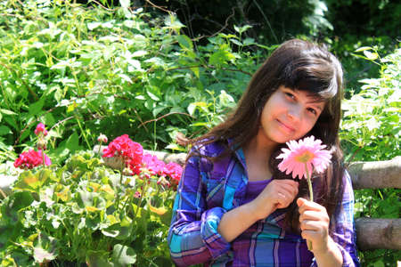 eight years old: Pretty eight year old girl sitting in the garden holding a pink flower Stock Photo