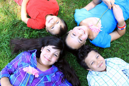 brothers and sisters: Four siblings consisting of two brothers and 2 sisters laying on the grass in the park